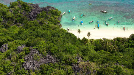 Sandy beach with tourists and tropical island by atoll with coral reef, top view. Lahos Island, Caramoan Islands, Philippines. Summer and travel vacation concept.