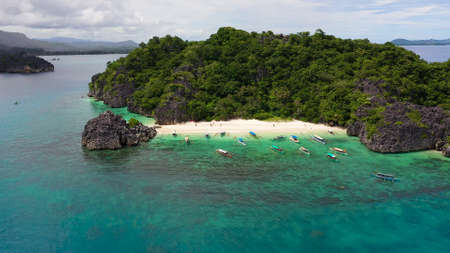 Tropical landscape: Lahos Island with beautiful beach and tourists by turquoise water view from above. Caramoan Islands, Philippines. Summer and travel vacation concept.