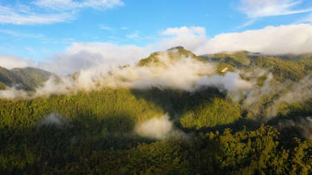 Aerial view of sunrise in the mountains covered with rainforest with clouds. Philippines, Mindanao.