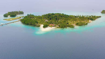 Island with beautiful beach, palm trees by turquoise water view from above. Malipano Islet, Philippines, Samal.