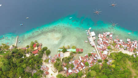 Aerial view of village of fishermen with houses on the water, with fishing boats, Samal island. Philippines, Mindanao.