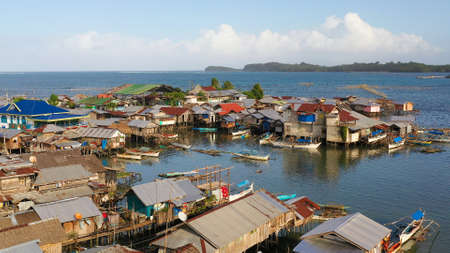 Fishing village with wooden houses on stilts in the sea. Village of fishermen with houses on the water, with fishing boats. Philippines, Mindanao. Standard-Bild - 156990552