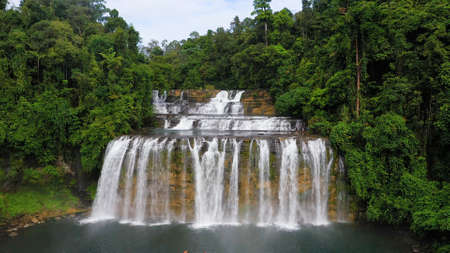 Beautiful waterfall in green forest, top view. Tropical Tinuy-an Falls in mountain jungle, Philippines, Mindanao. Waterfall in the tropical forest.