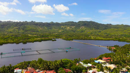 Fish farm on the background of mountains with forest and sky with clouds. Fish farm on Bohol island, Philippines.