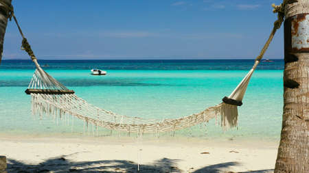 Tropical beach with with hammock and palm trees. Beautiful beach and tropical sea. Panglao island, Bohol, Philippines. Summer and travel vacation concept.