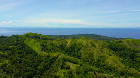 Hills and mountains covered with green grass against a background of blue sky and clouds. Bohol, Philippines. Summer landscape.