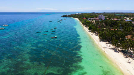 Tropical sandy beach with palm trees and turquoise clear waters. Alona beach, Panglao island, Philippines.
