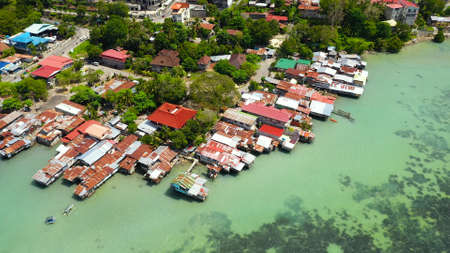 Village of fishermen with houses on the water, with fishing boats in Tagbilaran city. Bohol, Philippines.