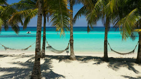 Beautiful tropical island with sand beach and hammock. Panglao, Philippines. Seascape with beautiful beach and palm trees.