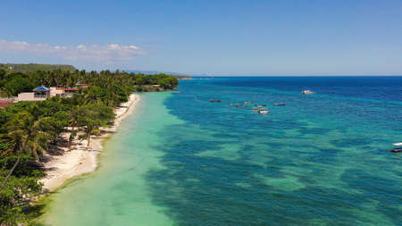 Beautiful tropical beach with white sand, palm trees, turquoise ocean. Alona beach, Panglao island, Bohol, Philippines.