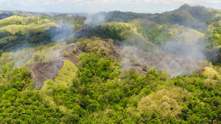 Aerial drone of Fire on hills with tropical vegetation. Farmers started a fire to expand their land. Bohol,Philippines. Standard-Bild - 156990637