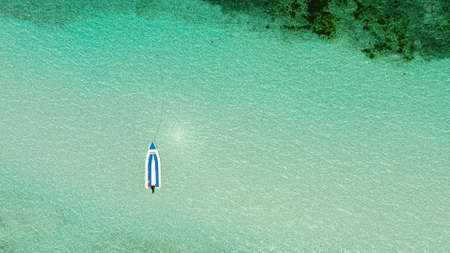 Sea surface in a turquoise lagoon with boat, top view. The texture of sea water. Transparent turquoise sea water, natural background. Summer and travel vacation concept.