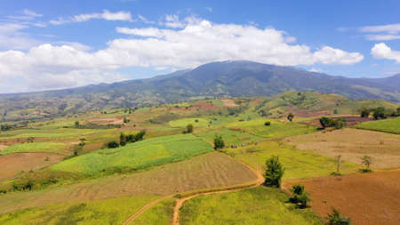Fertile farmlands with growing crops and mountains with clouds against a blue sky. Mindanao, Philippines.