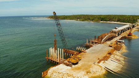 桩驾驶安装混凝土堆。重型建筑设备和工人建设海峡两岸。瑞利索尔加