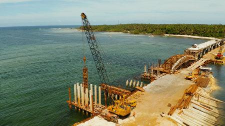 施工现场打桩机。正在施工的大桥横跨海湾,施工设备和工人在桥上。Siargao、菲律宾。
