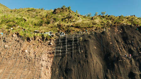 Workers strengthen the slope of the mountain with metal mesh preventing rockfall and landslide on the road, above view. workers constructing anti-landslide concrete wall prevent protect against rock slides. safety concept