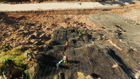 Protection of road from mountain slough, rockfall with metal accumulative restraining net fences. Workers constructing anti-landslide concrete wall prevent protect against rock slides. Rockfall protection. Workers strengthen the slope of the mountain with steel grid preventing rockfall and landslide on the road. 版權商用圖片