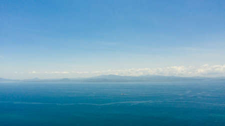 Blue sea and the tropical island of Basilan with mountains. Seascape with a tropical island. Zamboanga, Mindanao, Philippines.