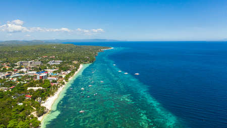 Aerial top view on sand beach,palm tree and ocean. Alona beach and azure water. Panglao island, Bohol, Philippines.