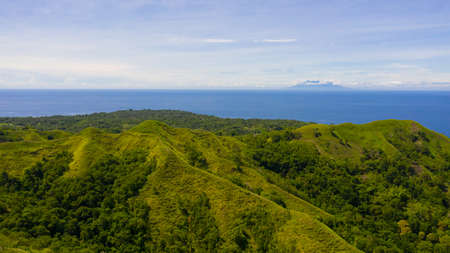 Aerial view of mountains and hills with rainforest and green grass under a blue sky with clouds on a Sunny summer day. Bohol, Philippines. Reklamní fotografie