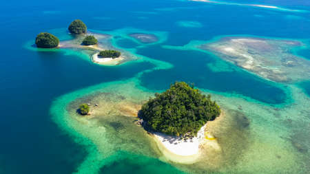 Aerial view of Tropical island with sand beach, palm trees by atoll with coral reef. Britania Islands, Surigao del Sur, Philippines.