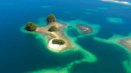 Island with a sandy beach and azure water surrounded by a coral reef and an atoll. Britania Islands, Surigao del Sur, Philippines.