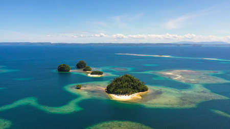 Tropical island with a sandy beach in turquoise water with a lagoon and a coral reef. Britania Islands, Surigao del Sur, Philippines. Reklamní fotografie