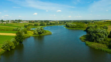 Aerial view of the river surrounded by green fields through which the river flows. Rural landscape in the countryside. Reklamní fotografie