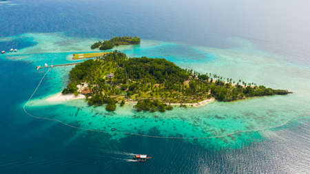 Aerial view of Tropical island with sand beach, palm trees by atoll with coral reef. Malipano island, Philippines, Samal.