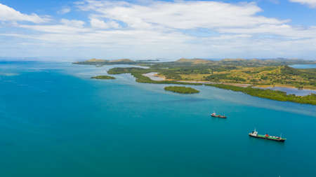 Aerial view of cargo ships leaving sea harbour at sunny day, islands on background. Tapal Wharf, Bohol, Philippines.