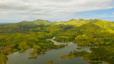 Aerial view of Lake among mountains and hills with rainforest and green grass under a blue sky with clouds on a Sunny summer day. Bohol, Philippines.