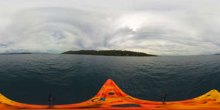 A man in a kayak at sea among the tropical islands. Philippines, Samal. 360 panorama VR.