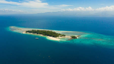 Tropical Little Liguid Island in the blue sea with beaches and palm trees. Little Cruz Island, Philippines, Samal.
