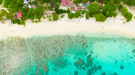 Aerial drone of sandy beach and azure water surrounded by a coral reef and an atoll. Alorro Beach, Philippines, Samal.