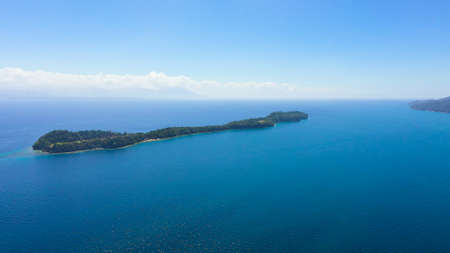 Top view of small tropical Big Liguid Island in the blue sea with a coral reef and the beach. Big Cruz Island, Philippines, Samal.