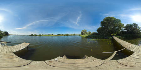 Summer landscape: lake with pier on the background of blue sky and clouds. 360VR.