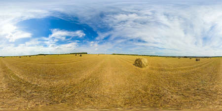 Rolls of haystacks on the field after harvest. Large wheaten field with cylindrical haystacks in summer day. 360VR. Standard-Bild