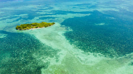 Tropical island and blue sea with a coral reef against the sky and clouds. Summer and travel vacation concept. Panglao, Philippines.