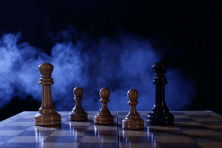 Wooden chess is a board game. Chess pieces on a dark background in smoke