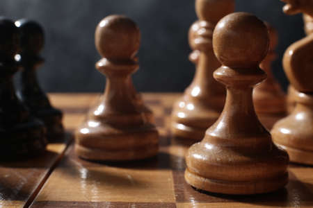 Wooden chess is a board game. Chess pieces on a dark background Imagens