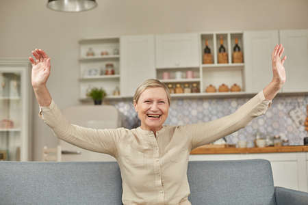 An elderly woman experiences the joy of being at home with her arms wide open. Happy pensioner concept