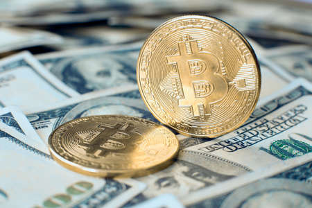 The gold bitcoin cryptocurrency coin stands on its own end, the second one lies on one hundred dollar bills Stock Photo