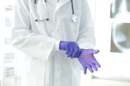 Doctor with stethoscope in a medical gown puts on protective gloves in a clinic