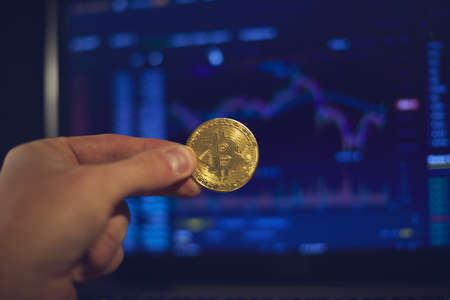A man holds a gold bitcoin coin in his hand. The graphs of changes in cryptocurrency rates are shown on the laptop monitor Foto de archivo