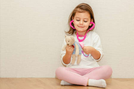Beautiful little girl pretending to be a nurse or doctor and auscultate her teddy-bear. Banco de Imagens