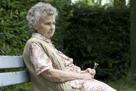 female senior adults: sad elderly woman in the park Stock Photo