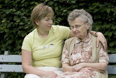 amigos abrazandose: anciana con su hija en el banco de parque