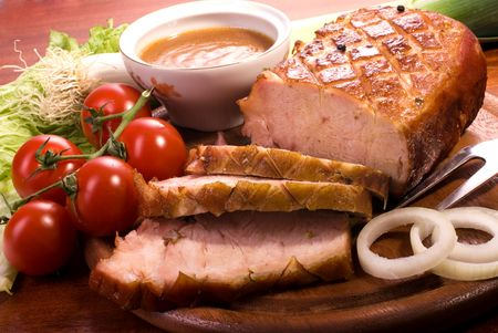 Close-up of a roast tenderloin pork served with vegetables