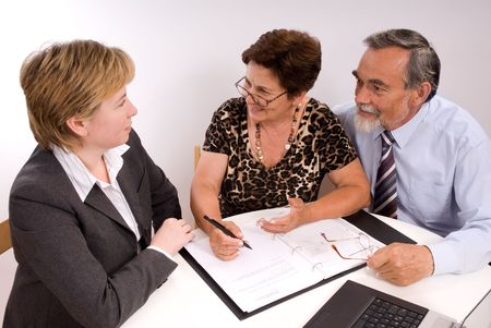 Mature couple talking to financial planner photo