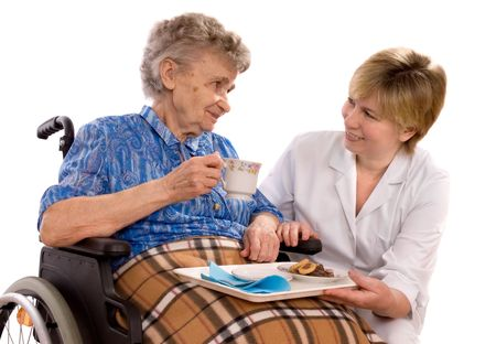 community health care: Health care worker and elderly woman in wheelchair needs help    Stock Photo